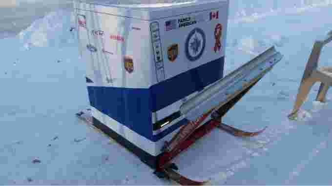 CBC: The ice resurfacer, which carries between 30 to 40 gallons of water, sports a Zamboni logo sticker, the Winnipeg Jets logo and various advertisements. The machine has a shovel blade attachment on the front to help clear snow off the ice surface, should the need arise. Skis were installed on the bottom for easier transportation. (Walther Bernal/CBC)