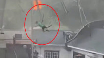 Caught on cam: Strong winds send restaurant employee flying onto roof