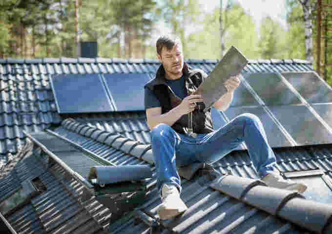 man installing solar panels credit: Mikael Vaisanen. The Image Bank. Getty Images.