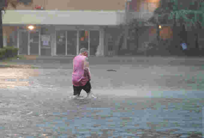 GETTY IMAGES: GULF SHORES, ALABAMA - SEPTEMBER 15: A man walks though a flooded parking lot as the outer bands of Hurricane Sally come ashore on September 15, 2020 in Gulf Shores, Alabama. The storm is bringing heavy rain, high winds and a dangerous storm surge from Louisiana to Florida. (Photo by Joe Raedle/Getty Images)